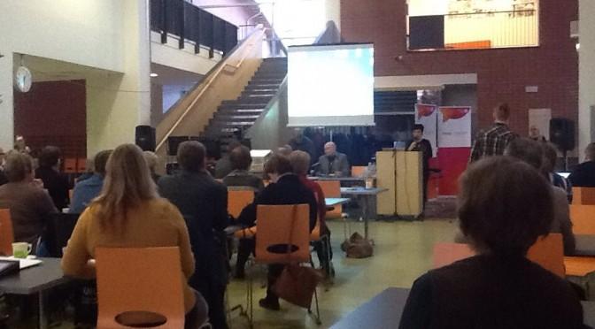 Kuvassa Oulun kaupunginhallituksen pj. RIikka Moilanen avaa tilaisuuden. Pöydän ääressä istuu yhteisötoiminnan päällikkö Pasi Laukka.